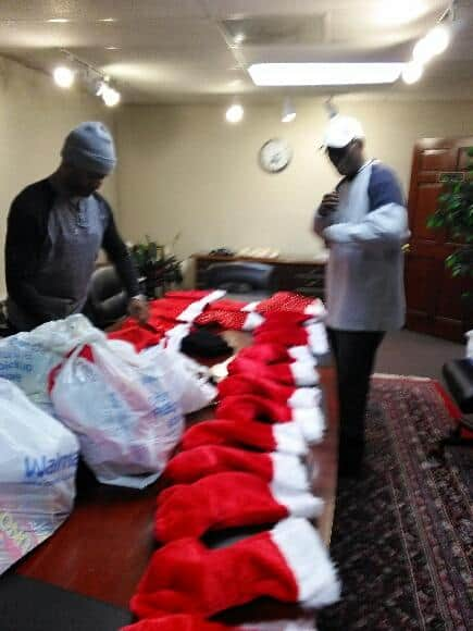 Santa Helpers AKA Mighty Men of Zion stuffing stockings.